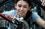 Woman repairing bicycle wheel in repair shop