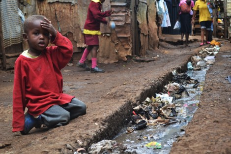 A young boy sits over an open sewer in the Kibera slum, Nairobi Photo Credit: Wikipedia